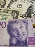 una banconota svedese di 20 corone svedesi e banconote in dollari, fondo e struttura americani immagini stock