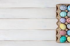 Una bandeja con los huevos de Pascua coloreados pintados disponibles en la superficie de madera blanca con el espacio a la izquie Imagenes de archivo