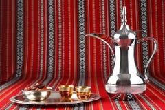 Una bandeja de tazas de té árabes se coloca en tela tejida árabe fotografía de archivo