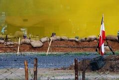 Una bandera alemana agita en el campo de batalla Fondo amarillo del humo Fotos de archivo libres de regalías