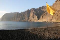 Una bandera amarilla cerca del Océano Atlántico en una playa Foto de archivo libre de regalías