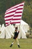 Una bandera americana temprana es volada por el solider en su manera de entregar el campo en el 225o aniversario de la victoria e Foto de archivo
