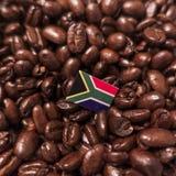 Una bandera de la República Surafricana colocada sobre los granos de café asados imágenes de archivo libres de regalías