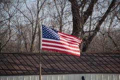 Una bandiera americana che soffia nel vento Immagini Stock Libere da Diritti
