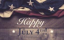 Una bandiera americana o una stamina su un fondo di legno con il saluto del 4 luglio Fotografie Stock