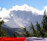 Una bandiera buddista rossa e bianca di preghiera con i alpines e il moun ripido Immagine Stock