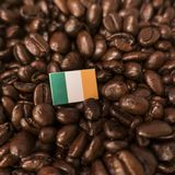 Una bandiera dell'Irlanda disposta sopra i chicchi di caffè arrostiti fotografie stock