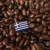 Una bandiera della Grecia disposta sopra i chicchi di caffè arrostiti fotografie stock libere da diritti