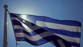 Una bandiera greca che ondeggia nel vento con un cielo blu archivi video