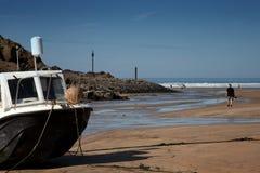 Una barca ancorata sulla sabbia dal mare Fotografia Stock Libera da Diritti