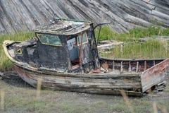 Una barca arrugginita abbandonata si siede in un campo di erba paludoso lungo Homer Spit, lungo la baia di Kachemak in Homer Alas immagine stock libera da diritti