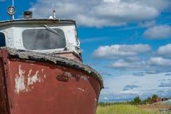 Una barca arrugginita rossa abbandonata e stagionata si siede in un'erba paludosa in Homer Alaska immagini stock libere da diritti