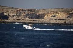 Una barca bianca di velocità sul mar Mediterraneo che lascia una traccia dello spruzzo di mare dietro  fotografia stock