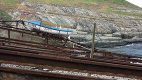 Una barca blu e bianca sulle rotaie ad un pilastro da pesca archivi video