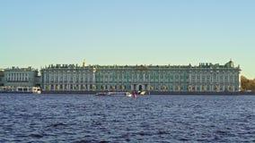 Una barca che galleggia sul fondo del palazzo di inverno in primavera, San Pietroburgo video d archivio