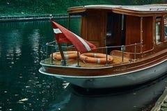 Una barca con la bandiera nazionale della navigazione della Lettonia nel parco vicino all'opera nazionale lettone a Riga, Lettoni fotografia stock