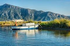 Una barca del pescatore in un lago calmo legato ad una linea costiera sabbiosa con il g fotografia stock