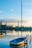 Una barca e un albero hanno attraccato da un lago blu Fotografie Stock Libere da Diritti