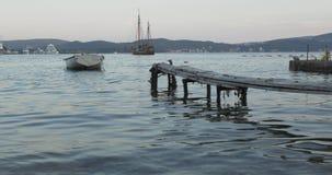 Una barca legata ad un pilastro di legno nel mare nella sera video d archivio