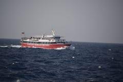 Una barca rossa e bianca sull'oceano immagine stock