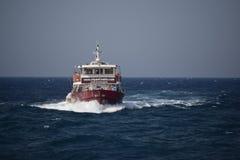 Una barca rossa e bianca sull'oceano fotografie stock libere da diritti