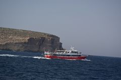 Una barca rossa e bianca sull'oceano con una grande roccia del mare nei precedenti fotografia stock libera da diritti