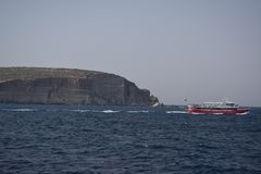 Una barca rossa e bianca sull'oceano con un fondo della roccia e del cielo blu del mare fotografia stock libera da diritti