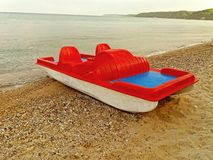 Una barca rossa sulla spiaggia greca fotografia stock libera da diritti