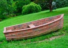 Una barca sconosciuta fatta del mattone su un prato inglese verde Ciò può essere usata come un simbolo di disfunzione, il disadat fotografie stock
