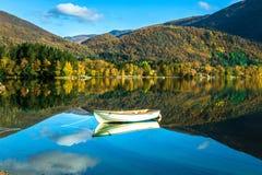 Una barca sola e montagne riflesse nel lago Haukeland in autunno vago, variopinto e tranquillo a Bergen, Hordaland, Norvegia fotografia stock libera da diritti