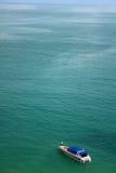 Una barca sola in mezzo al mare profondo Fotografie Stock