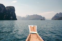 Una barca sola nell'oceano fra le rocce fotografia stock