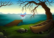 Una barca sotto l'albero vicino al mare con un grande pesce Fotografie Stock