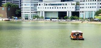 Una barca sta traversando il fiume di Singapore Immagine Stock