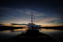Una barca traversa il fiume di Javari dopo il tramonto immagini stock