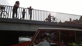 Una barca turistica naviga sotto il ponte a Copenhaghen Sulla gente del ponte che guarda sul canale Fotografie Stock Libere da Diritti