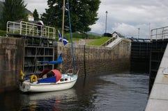 Una barca a vela attraverso un loch Immagini Stock