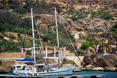 Una barca a vela blu nel porto fotografie stock