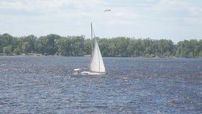 Una barca a vela di bianco naviga lungo il fiume nei precedenti di una foresta sulla riva stock footage