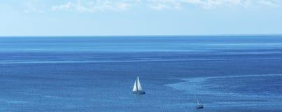 Una barca a vela sola in blu immagini stock