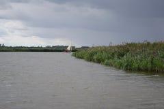 Una barca a vela su un fiume in Norfolk Broads, prima di pioggia fotografia stock libera da diritti