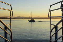 Una barca a vela tira un motoscafo nelle acque calme di un lago al tramonto immagini stock libere da diritti