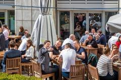 Una barra al aire libre en Canary Wharf embaló con la consumición de la gente Foto de archivo libre de regalías