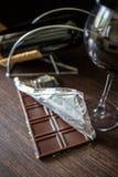 Una barra de chocolate en hoja con el vidrio de vino rojo Fotografía de archivo