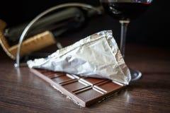 Una barra de chocolate en hoja con el vidrio de vino rojo Imagenes de archivo