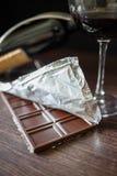 Una barra de chocolate en hoja con el vidrio de vino rojo Imagen de archivo libre de regalías
