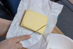 Una barra de la mantequilla en un tablero de madera con un cuchillo foto de archivo