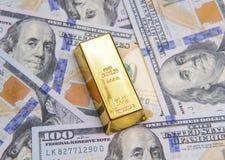 Una barra de oro con los nuevos billetes de dólar del americano ciento foto de archivo