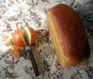 Una barra de pan, cebollas cortadas y un cuchillo en un mantel ligero de lino fotografía de archivo libre de regalías