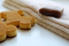 Una barra marrone del sapone, un asciugamano beige e pezzuola per lavare due sotto forma di cane e di osso Vista laterale e primo fotografia stock